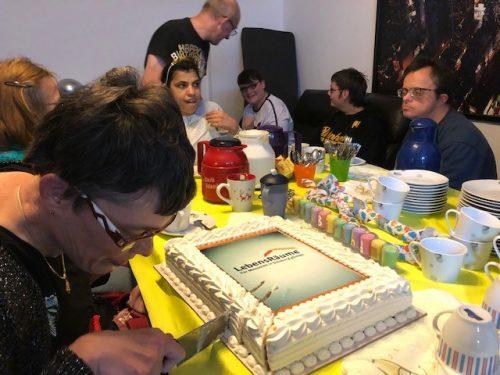 Bewohnerinnen und Bewohner sitzen zusammen und Essen Kuchen.
