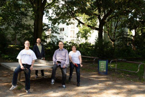 Vier Menschen stehen mit Tischtennisschlägern an einer Tischtennisplatte.