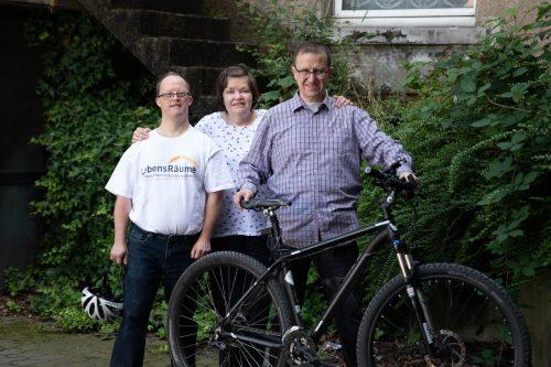 Drei Menschen zusammen. Einer von ihnen hält ein Fahrrad fest.