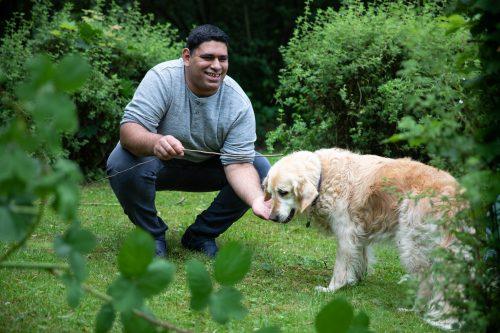 Ein Mann spielt mit einem Hund.
