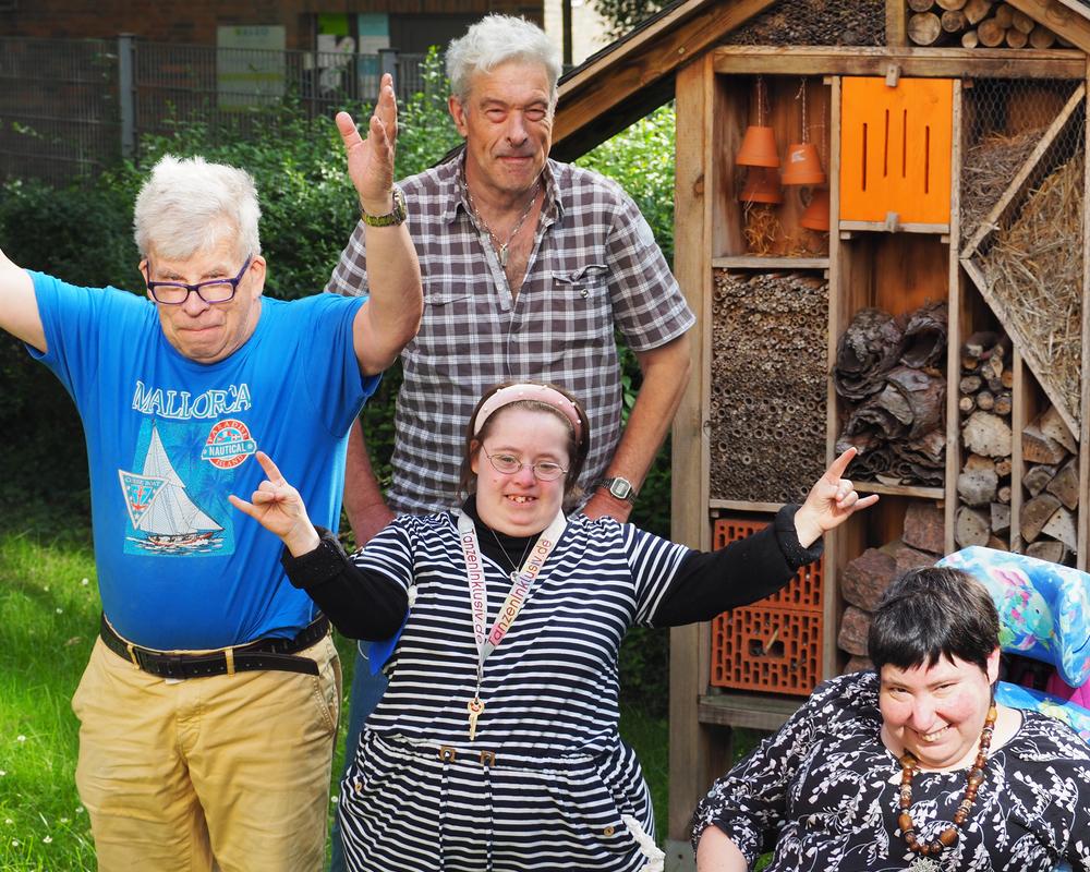 Aufnahme von vier Menschen, die zusammen in einem Garten stehen und in die Kamera lächeln. Zwei von ihnen strecken freudig die Arme in die Luft. Es handelt sich um den Bewohnerbeirat der Wohnstätte.