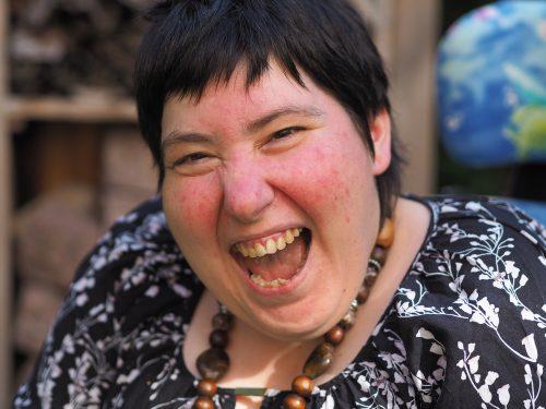 Aufnahme einer Frau, die lachend in die Kamera blickt.
