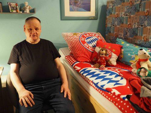 Bewohner Hans-Jürgen Klemcke sitzt auf einem Stuhl und blickt in die Kamera. Neben ihm ist sein Bett zu erkennen, das mit einer Bayern-Muenchen-Decke bezogen ist.