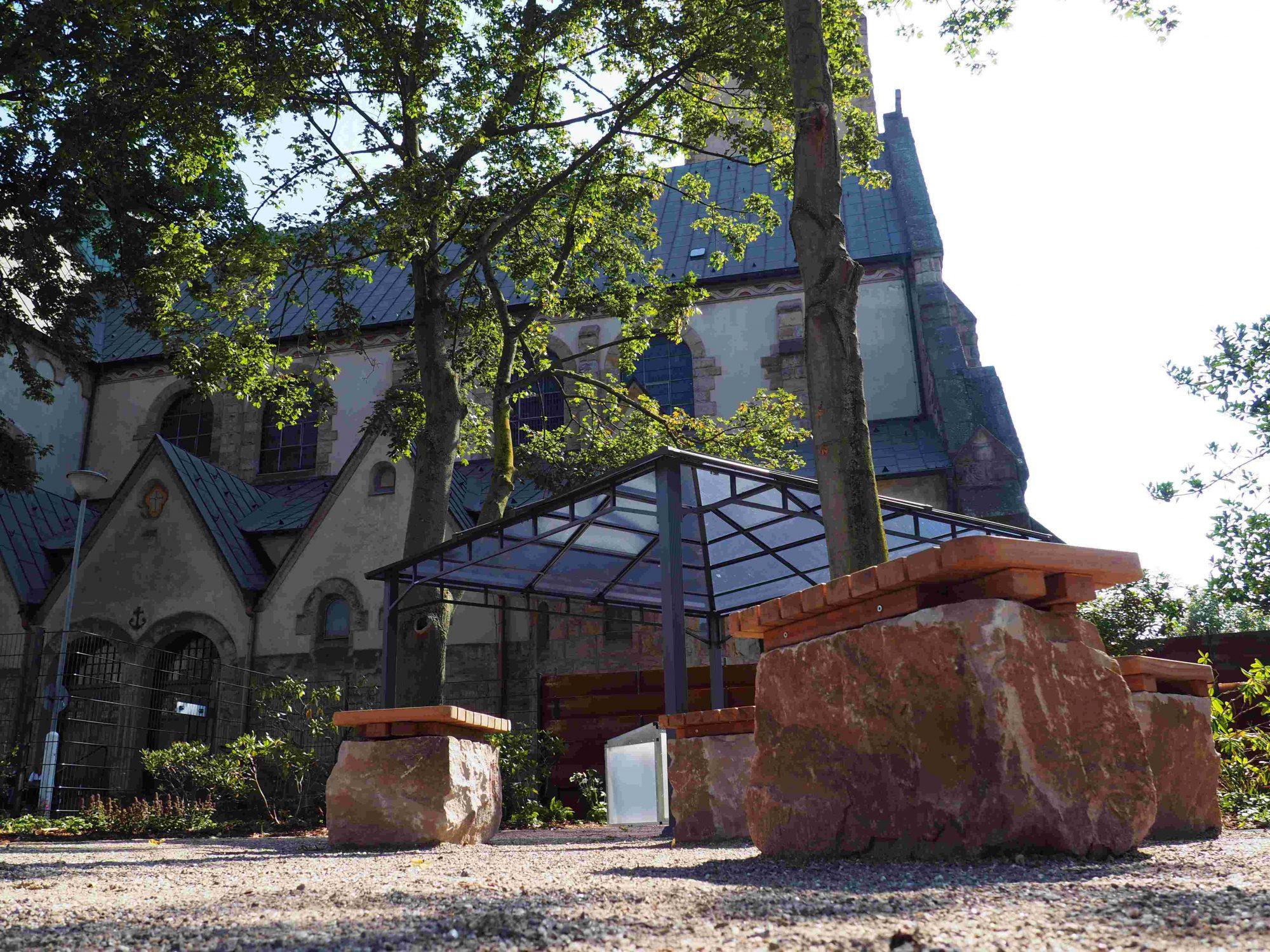 Aufnahme des Pavillons des Hochfelder Hofgartens. Im Hintergrund ist eine Kirche zu sehen.