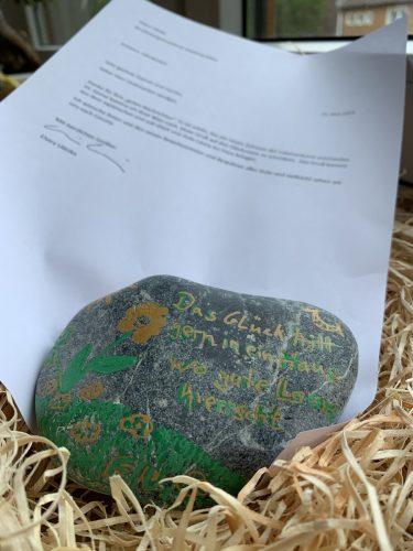 Aufnahme eines bemalten Steins und eines Begleitschreibens.