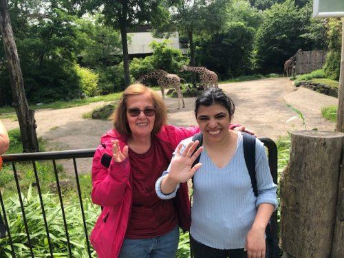 Aufnahme von zwei Frauen, die in die Kamera lächeln und winken. Im Hintergrund sieht man zwei Giraffen.