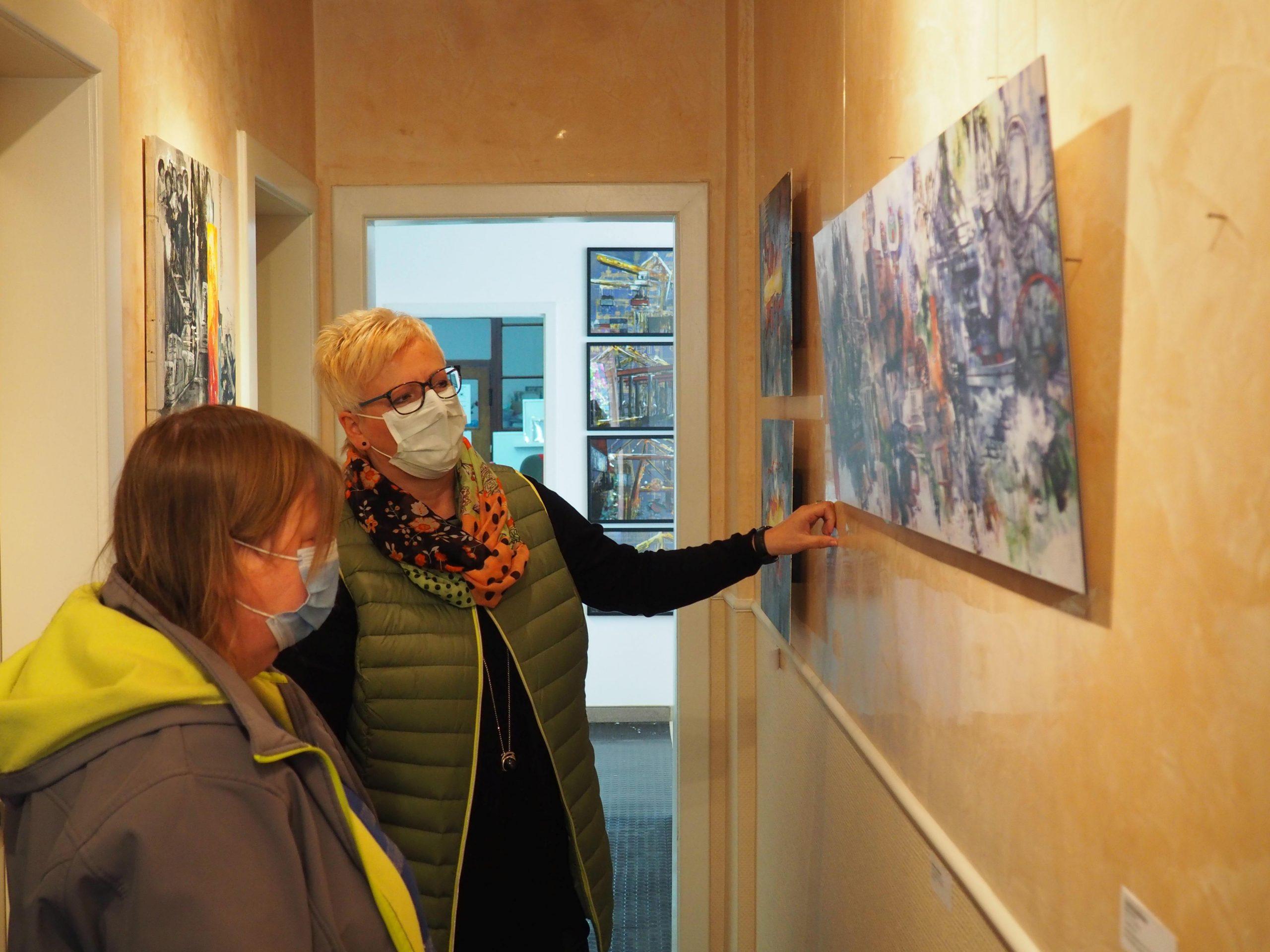 Dorothee Impelmann und Rosemarie Jaroniak betrachten ein Bild der Künstlerin.