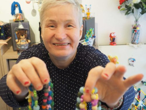 Aufnahme von Petra Schäfer, die lächelnd zwei Perlenketten in die Kamera hält.