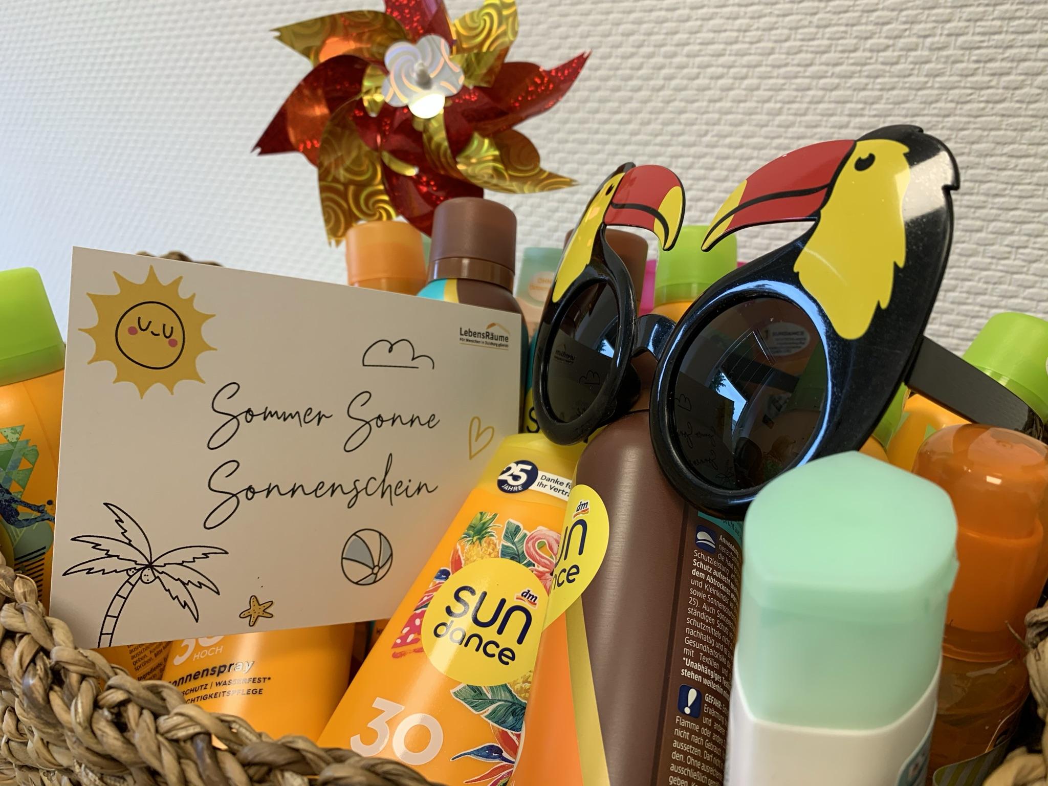 """Aufnahme eines Korbs, der gefüllt ist mit Sonnencreme und einer Sonnenbrille. Ebenfalls ist eine Karte zu sehen auf der """"Sommer Sonne Sonnenschein"""" geschrieben steht."""