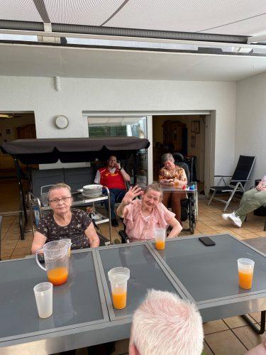 Aufnahme von mehreren Menschen, die auf einer Terasse sitzen und in die Kamera lächeln.