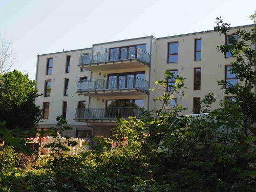 Aufnahme der Wohnstätte an der Wanheimer Straße 155. Zu sehen ist ein helles Gebäude von außen betrachtet, das von grünen Pflanzen umrandet wird.