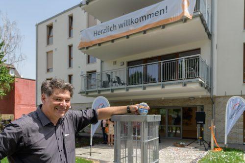 Geschäftsführer Marcus Guttmacher-Jendges füllt einen Stein in eine Installation. Im Hintergrund ist die neue Wohnstätte zu erkennen.