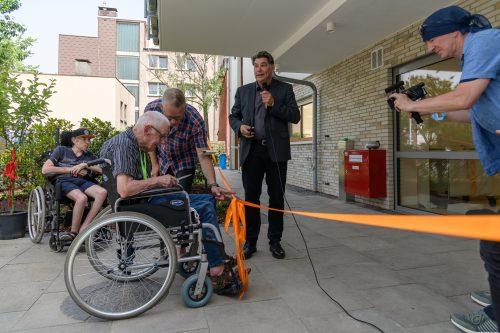 Aufnahme eines Manns im Rollstuhl, der ein Band durchschneiden möchte.