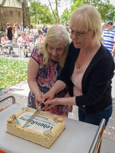 Aufnahme von zwei Frauen, die gemeinsam eine Torte anschneiden, die das LebensRäume-Logo trägt.