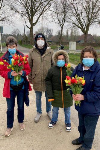 Bewohner der Lebensräume Duisburg mit drei bunten Tulpensträußen in der Hand.