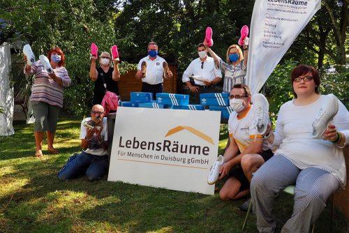 Gruppenbild mit acht Bewohnern der Wohnstätte Fischerstraße 4-8, die Lions-Schuhe mit den Händen hochhalten.