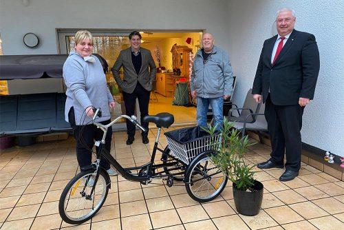 Landtagsabgeordneter besucht die Wohnstätte Kurfürstenstraße: Abbildung von vier Personen mit Dreirad in der Mitte und Pflanze.