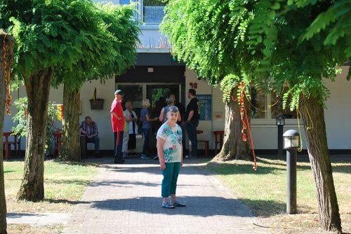 Eine Bewohnerin steht auf dem Weg zur Eingangstür zwischen geschmückten Bäumen.