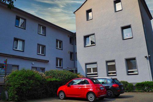 Außenansicht der Wohnstätte in der Wanheimerstraße 355: zwei weiß-graue Häuser mit Fenstern, grünen Büschen und zwei Autos davor