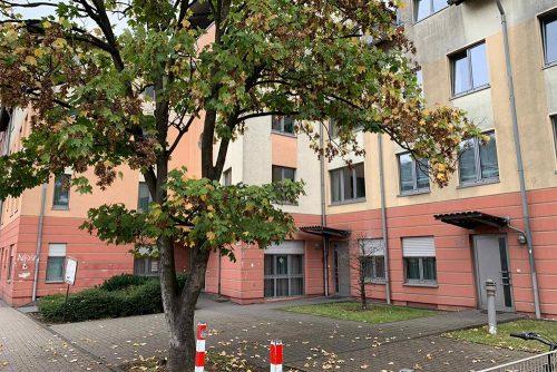 Außenansicht der Wohnstätte Wanheimerstraße: gelb-rotes Haus mit Fenstern, Eingangstüren und Baum vor dem Haus.