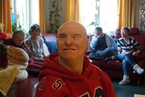 Bewohner im roten Pullover, im Hintergrund vier weitere Bewohner sitzend auf einem Sofa.