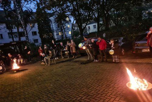 Menschen mit Laternen stehen oder sitzen um zwei Lagerfeuer.