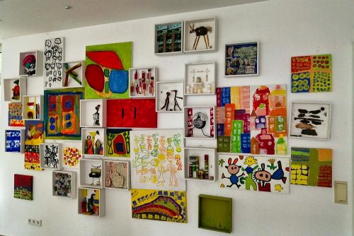 Wand in der Wohnstätte Wanheimerstraße: bunte Bilder und kleine Regale mit gebastelten Figuren.