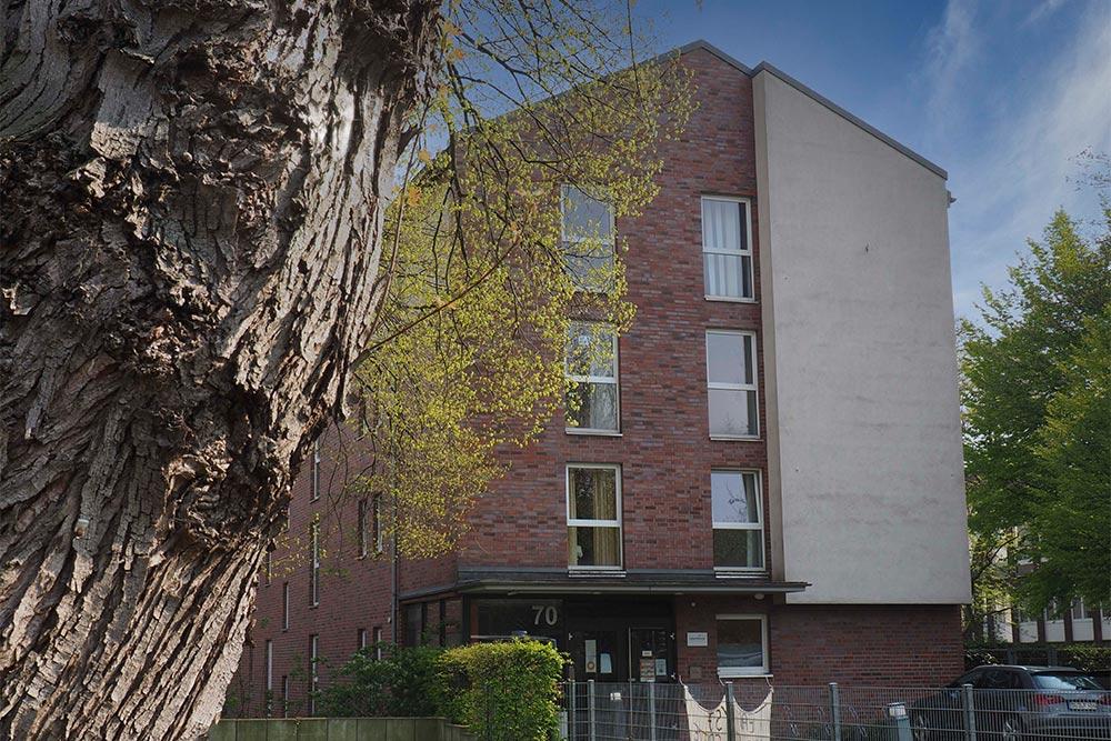 Außenansicht der Wohnstätte in der Wintgensstraße 70: Rot-weißes Backsteinhaus mit Fenstern und Eingangstür
