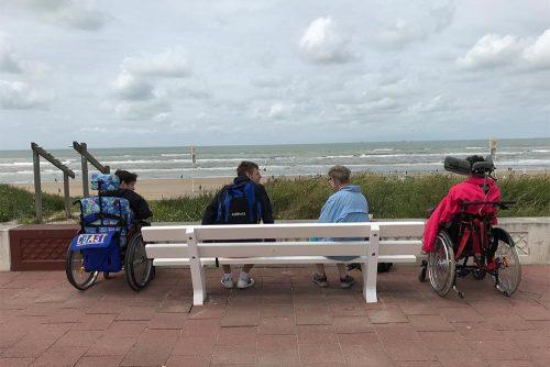 Vier Bewohner der Wohnstätte sind von hinten zu sehen mit Blick auf Dünen, Strand, Meer und Wolken.