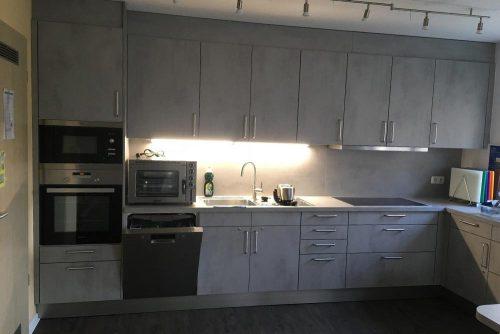 Abbildung der Küche in der Wohnstätte Wintgensstraße 70: Moderne graue Einbauküchenzeile mit zwei Öfen, Herd und Spüle.