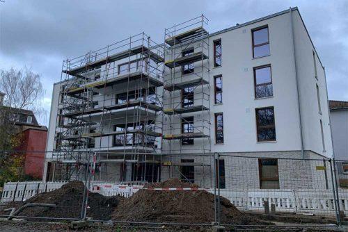 Ansicht des Neubaus der LebensRäume Wohnstätte auf der Wanheimer Straße 155 in Duisburg mit Bauzäunen vor zwei Erdaufwürfen